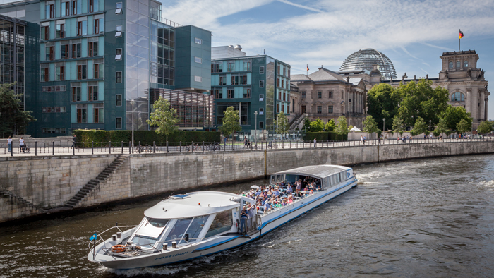 Tourist boats on The Spree pass by the German Reichstag